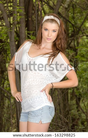 Casually dressed young girl with long hair posing in the bush