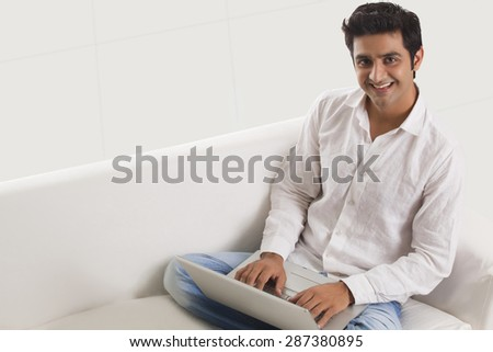 Casually dressed young man on sofa using laptop at home - stock photo