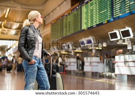 Casually dressed young stylish female traveller checking a departures board at the airport terminal hall in front of check in couters. Flight schedule display blured in the background. Focus on woman. - stock photo