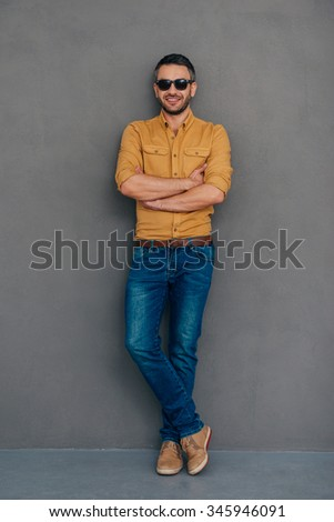Casually handsome. Full length of confident mature man in sunglasses keeping arms crossed and looking at camera with smile while standing against grey background - stock photo