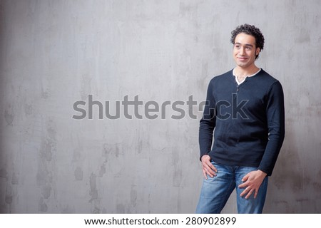 Casually handsome. Handsome young arabic man holding hand in pockets and looking at camera while standing against grey background - stock photo