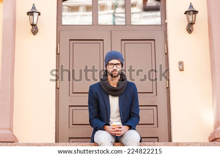 Casually handsome. Handsome young man in smart casual wear sitting in front of the house entrance and holding coffee cup  - stock photo