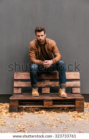 Casually handsome. Handsome young man sitting on the wooden pallet and looking at camera with grey wall in the background and orange fallen leaves on the floor  - stock photo
