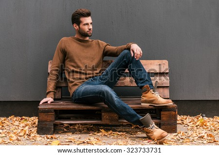 Casually handsome. Handsome young man sitting on the wooden pallet and looking away with grey wall in the background and orange fallen leaves on the floor  - stock photo