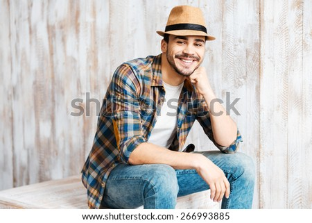 Casually handsome. Handsome young man wearing hat and looking at camera while sitting against the wooden wall  - stock photo