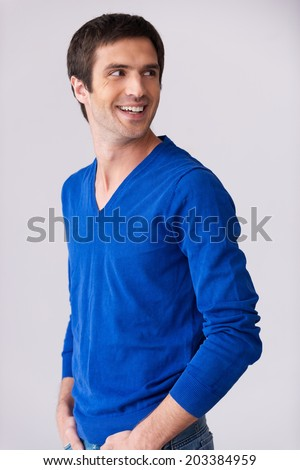 Casually handsome. Side view of handsome young man in blue sweater looking over shoulder and smiling while standing against grey background - stock photo