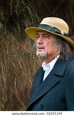 Casuarina Cowboy - Middle aged man with long hair and old straw hat near casuarina tree - stock photo
