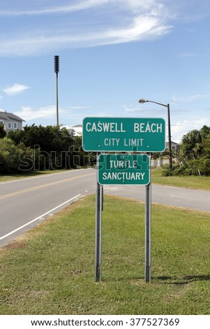 Caswell Beach, NC, USA - September 29, 2015: Green and white Caswell Beach City Limit and Turtle Sanctuary signs. Caswell Beach City Limit and Turtle Sanctuary Sign - stock photo