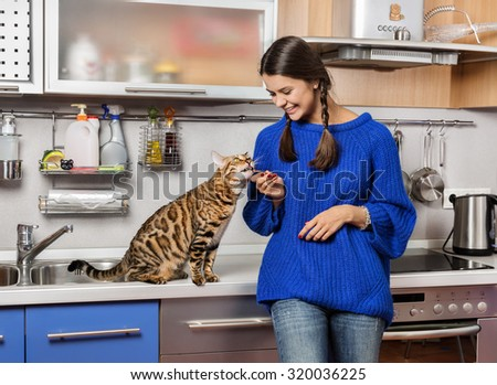 Cat and girl in the kitchen. - stock photo