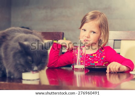 Cat and little girl drinking milk. The image is tinted. - stock photo