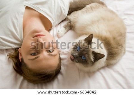 Cat and woman looking up from a white bed. - stock photo
