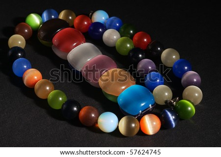 Cat's eye quartz bracelet and necklace on black textured background with selective focus - stock photo