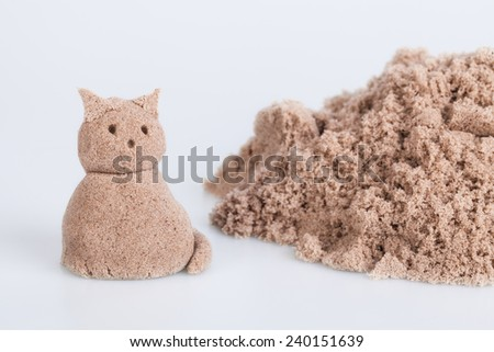 Cat sculpture from wet sand on a white background - stock photo