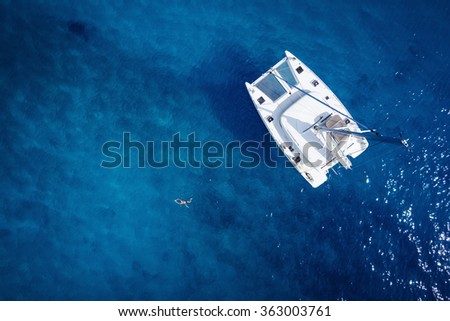 Catamaran in open sea - aerial / drone view - stock photo