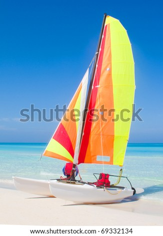 Catamaran on a beautiful beach in the caribbean. - stock photo