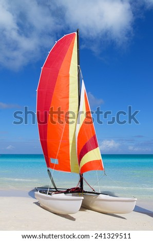 Catamaran with its colorful sails wide open on Cuban white sandy beach - stock photo
