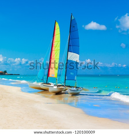 Catamarans with their colorful sails spread out on Varadero beach in Cuba - stock photo