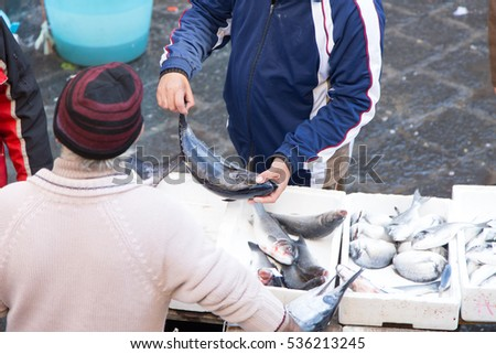 Catania, Italy - December 10, 2016: Fisherman cuts fish to the fish market in Catania, Sicily, Italy. Today is one of the tourist attractions of the city
