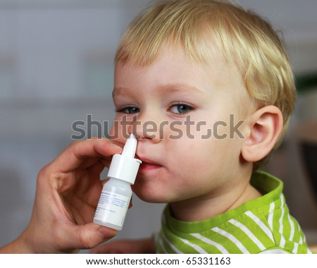 Catarrh - Mother spraying 2 years old baby boy medicine in nose, nose drops, nose spray. - stock photo