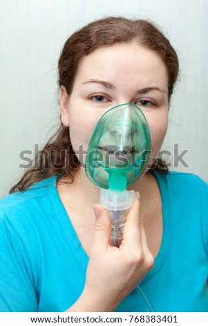 Catch cold woman with sore throat making inhalation itself with mask on her face. Nebulizer device