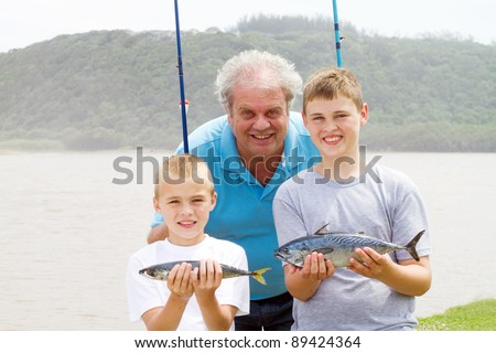 catch of the day: happy grandpa and grandson showing two fish - stock photo