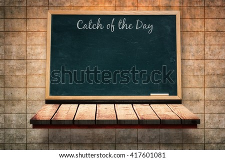 Catch of the day message against black board on a wooden shelf