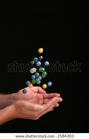 Catching a group of falling marbles against a black background - stock photo