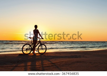 Catching a moment in time. Young sporty woman cyclist silhouette contemplating the sunset on blue sky background on the beach. Summertime multicolored outdoors horizontal image with filter. - stock photo