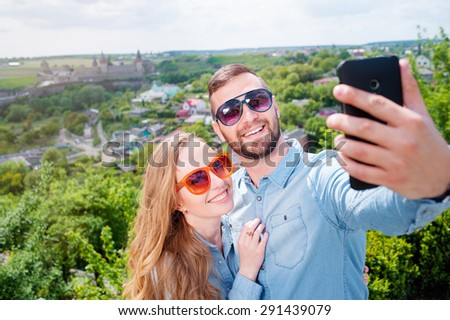 Catching the bright life moments. Beautiful young loving couple taking selfie with smart phone and smiling while traveling by Europe. - stock photo