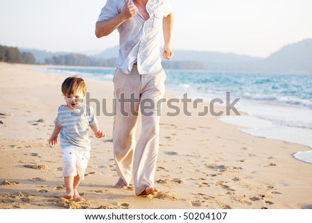 cate little boy racing with his father along the beach - stock photo