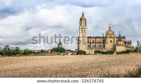 Catedral de Santa Maria de Segovia in the historic city of Segovia with dramatic cloudscape, Castilla y Leon, Spain - stock photo