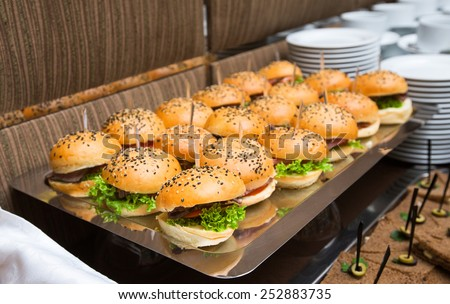 Catering american style - served table with plenty of hamburgers and other snacks - stock photo