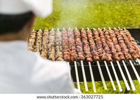 Catering chef cooking meat on outdoor bbq grill - stock photo