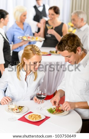Catering company event young colleagues eating at buffet party - stock photo