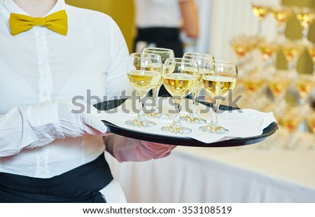 catering or celebration concept. female waitress holding a tray with glasses of wine at party, Authentic shot in mixed light conditions - stock photo