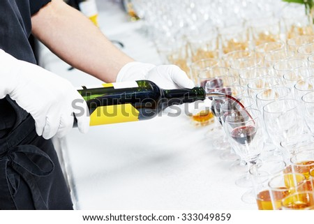 Catering or celebration concept. Male waiter hand pouring  glass of red wine during catering service at party - stock photo