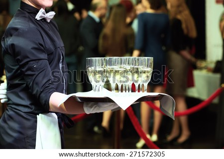 catering or celebration concept. Waiter holding a tray with glasses of vine at party - stock photo