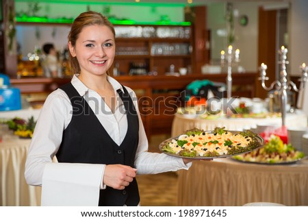Catering service employee or waitress posing with a tray of appetizers - stock photo