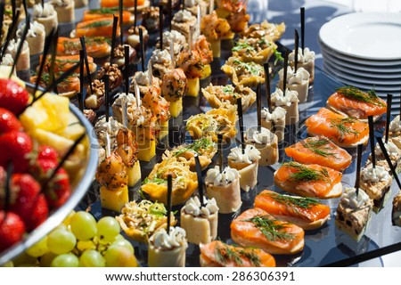 Catering service plate .appetizing sandwiches on plastic sticks rangeSandwiches on a table the buffet. meat, fish, vegetable canapes on a festive wedding table outdoor - stock photo
