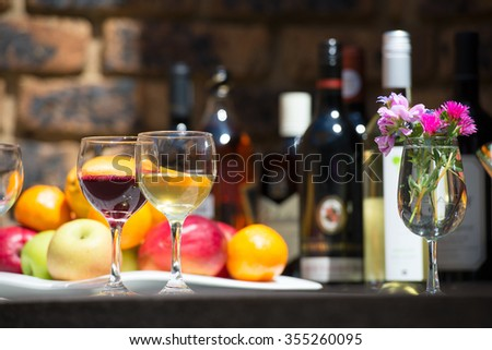 Catering service with two glasses red and white wine, fruits and alcohol bottles on bartender background
