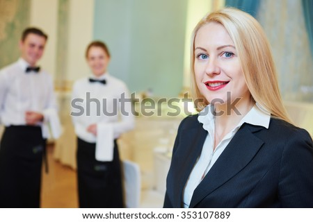Catering services. Restaurant manager portrait in front of waitress and waiter staff at banquet hall - stock photo