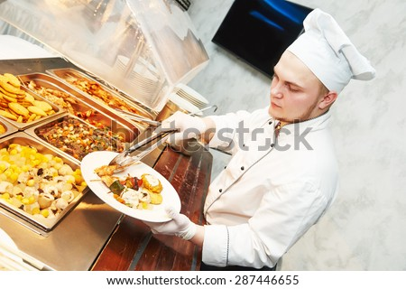 Catering services. young cook chef serving food at buffet - stock photo