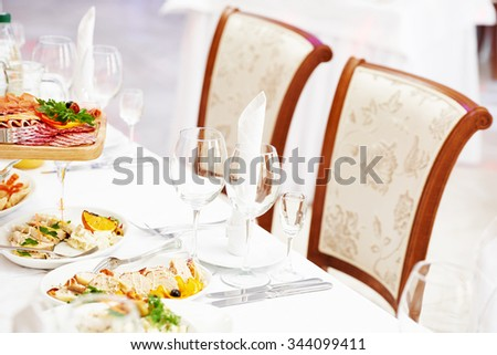 catering table set service with silverware, glass stemware and napkin at restaurant before party - stock photo