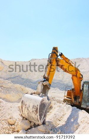 Caterpillar excavator in chalk pit against a blue sky