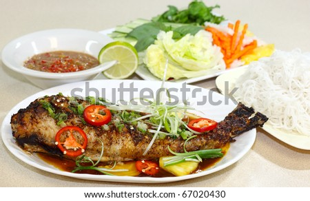 Catfish baked with oyster sauce  and herbs, Vietnamese cuisine - stock photo