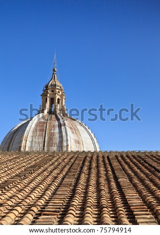 Cathedral dome and terracotta roof against clear blue sky. - stock photo
