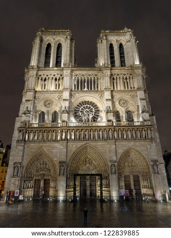 Cathedral of Notre Dame of Paris illuminated by night with a man taking a picture in front of the church, Paris, France.