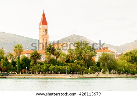 Cathedral of St. Lawrence  a Roman Catholic triple-naved basilica constructed in Romanesque-Gothic in Trogir, Croatia. UNESCO World heritage. And a boat on the Adriatic Sea - stock photo