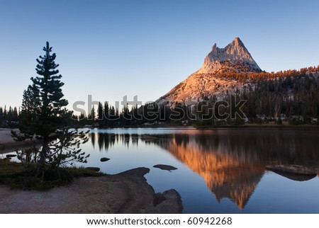 Cathedral Peak and Pine are Reflected in Upper Cathedral Lake - stock photo