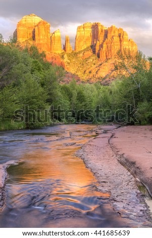 Cathedral Rock is reflected in a slickrock channel on Oak Creek in Red Rock Cross-Crescent Moon Park in Sedona, Arizona